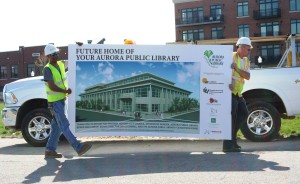 Two members of the R.C. Wegman Construction team get ready to install a sign before the Aurora Public Library groundbreaking on May 1.