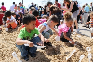 "Children dig for buried ""gold"" coins during groundbreaking festivities for the Aurora Public Library's new building in downtown Aurora. Once coins were discovered, children could turn them in for a prize."